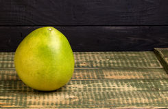 Fruit of a pummelo on an wooden table. Fruit of a pummelo on an old wooden table Stock Photo