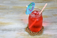 Fruit punch in mason jar with paper umbrella. Red fruit punch drink in glass mason jar with paper umbrella and gingham straw on rope coaster Royalty Free Stock Image