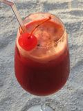 Fruit red drink, on the white sand. Stock Photography