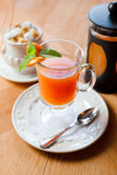 Fruit red tea with orange in glass cup, on wooden table Stock Image