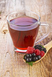 Fruit red tea with wild berries in wooden spoon Stock Photos