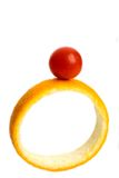 Fruit ring. A red cherry tomato placed on top on an orange ring against white background Royalty Free Stock Photography