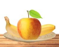 Fruit rouge et jaune de pomme avec la feuille et la banane vertes dans le plat i Photo libre de droits