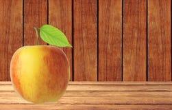Fruit rouge et jaune de pomme avec la feuille verte sur la table en bois Photographie stock