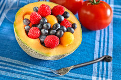 Fruit`s. Mixed fruits inside melon on blue background Stock Images