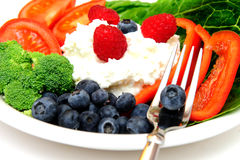 Fruit Salad. Closeup of a cottage cheese salad with vegetables and berries including Raspberry, Blueberry, Red Bell Pepper, Broccoli, Tomato on a bed of Romain Royalty Free Stock Images