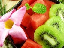 Fruit salad. Fresh fruit salad whit flowers background royalty free stock photography