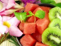 Fruit salad. Fresh fruit salad whit flowers background royalty free stock images