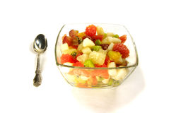 Fruit salad. In salad-bowl with spoon isolated over white, ingredients are kiwi, grapefruit grapes pear tangerine orange Stock Photo