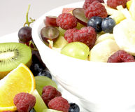 Fruit salad. White bowl with mixed fruits decorated with a kiwi half, an orange quarter, grapes and raspberries on the side Stock Images
