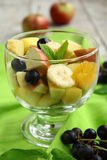Fruit salad. In a glass bowl on a green cloth Royalty Free Stock Images