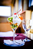 Fruit salad. With cream served in glass in restaurant, ambient light Royalty Free Stock Images