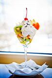 Fruit salad. With cream served in glass in restaurant, ambient light Stock Images