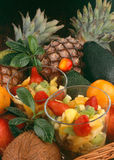 Fruit salad. In two glass bowls, surrounded by various fruit Stock Image