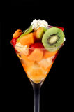 Fruit Salad. Fresh fruit salad and cream in a tall glass, with black background royalty free stock photo