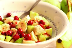 Fruit salad. White ceramic bowl full of fruit, bananas, apples, sour cherries Stock Images