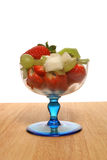 Fruit salad. In a sundae glass on a wooden surface Stock Photos