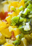 Fruit salad. Closeup of a tasty fruit salad made of kiwis and oranges royalty free stock photo