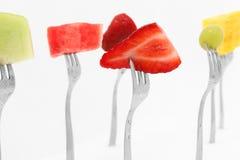 Fruit Salad. On forks over white.  Strawberry, watermelon, honeydew, grape, pineapple Stock Image