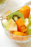 Fruit salad. Glassy plate with Fruit Salad (fruit: kiwi, apple, grape, persimmon) and fruit-fork on the ribbed white napkin stock photos