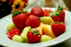 Fruit Salad 9135. Fruit Bowl shown with strawberries, honeydew, cantaloupe and watermelon.  Floral boquet centerpiece in background Royalty Free Stock Image
