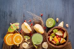 Fruit salad of apples, bananas, orange and pomegranate in half a coconut and fresh green smoothies from vegetables, lime and mint Stock Photo