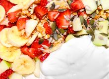 Fruit salad background, strawberries, banana, nuts and seeds, white plain yoghurt. Colorful summer food concept. Fruit salad background, strawberries, banana Royalty Free Stock Images