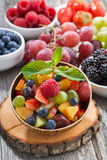 Fruit salad in a bamboo bowl and fresh berries, vertical Stock Photo