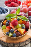 Fruit salad in a bamboo bowl and fresh berries, vertical Stock Photography
