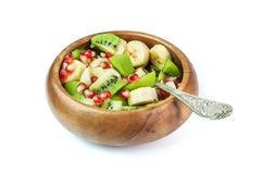 Fruit salad with banana, kiwi and pomegranate in a wooden bowl,. Fruit salad with banana, kiwi and pomegranate Stock Images