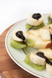 Fruit salad with banana and kiwi topped with chocolate cream Stock Photos