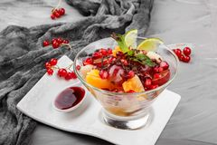 Fruit salad with banana, orange, grapes and pomegranate in glass bowl on grey background. Healthy breakfast royalty free stock photos