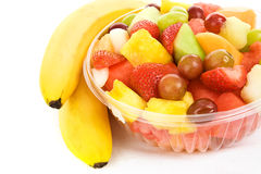 Fruit Salad with Bananas. Bowl of juicy, delicious fruit salad beside two bananas.  Isolated on white Royalty Free Stock Images