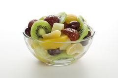 Fruit salad in a bowl. Fruit salad desert in a transparent bowl on a white background Stock Photos