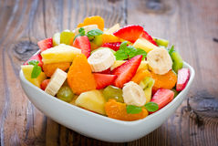 Fruit salad in the bowl. On the wooden table Stock Photos