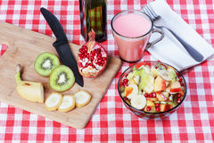 Fruit salad, a bowl of dark glass, cutting board. Stock Image
