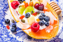 Fruit salad bowl with fruits, berries and nuts. Stock Photo