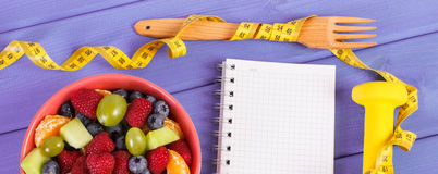 Fruit salad, centimeter with dumbbells and notepad for writing notes, healthy lifestyle and nutrition concept. Fresh fruit salad, tape measure, dumbbells for Stock Photography