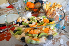 Fruit salad in a clear glass bowl. Different fruits such as bananas, kiwis, oranges, pears and apples mixed in a fruit salad in a glass bowl on a dining table stock photos