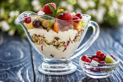 Fruit salad closeup with berries, yogurt and granola in a glass bow Stock Photo