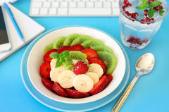 Fruit salad concept of a healthy snack at work. Stock Images