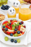 Fruit salad, cream and painted eggs for breakfast Stock Photos
