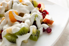 Fruit salad drizzled with ice cream. Close-up on a white plate Stock Photo