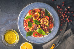 Fruit salad with fig and cherry tomatoes on the ceramic plate  on the stone table horizontal Royalty Free Stock Photo