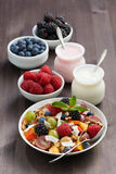 Fruit salad, fresh berries and yoghurts on a wooden table Royalty Free Stock Photo