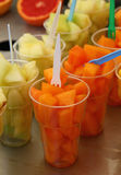 Fruit salad of fresh melon cubes in plastic cups Royalty Free Stock Images