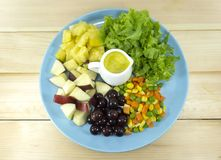 Fruit salad with fresh vegetables in a blue plate royalty free stock image