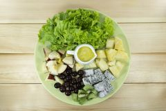 Fruit salad with fresh vegetables in a green plate royalty free stock photos