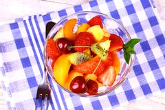 Fruit salad in glass bowl and dessert fork Royalty Free Stock Photo