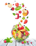 Fruit salad in glass bowl with ingredients in the air Royalty Free Stock Photo
